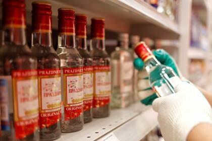 Un empleado de un supermecado en Moscú coloca botellas de vodka en los estantes en medio del alto consumo de alcohol en el país detectado por la pandemia. April 8, 2020. REUTERS/Maxim Shemetov