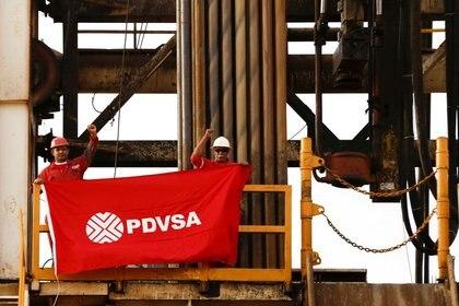 Trabajadores de un campo petrolero sostienen una bandera con el logotipo corporativo de la petrolera estatal venezolana PDVSA, en una plataforma de perforación de un pozo petrolero operado por ellos, en el cinturón de Orinoco, Venezuela. (Foto: REUTERS/Carlos García Rawlins).