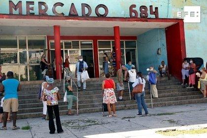 Varias personas esperan para entrar en un mercado a comprar productos, en La Habana (EFE/ Ernesto Mastrascusa)