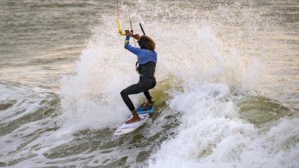 Una foto tomada el 10 de octubre de 2019 muestra a un kitesurfista surfeando olas en la playa. (AFP)