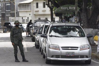 Un miembro de la Guardia Nacional junto a una cola de autos esperando para repostar en una gasolinera de PDVSA en Caracas (Foto: Carlos Becerra)