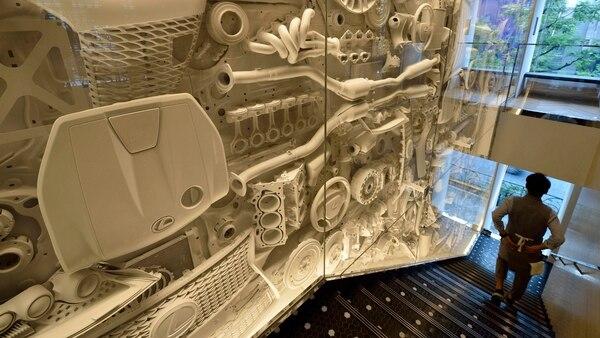 Piezas originales de automóviles Lexus pintadas en blanco decoran la pared vidriada del complejo de cuatro pisos