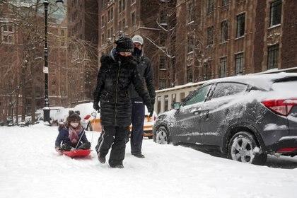 Una mujer lleva a su hijo en un trineo en Manhattan (REUTERS/Carlo Allegri)