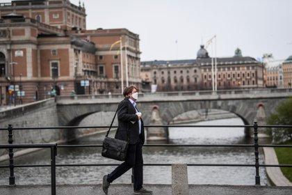 Un hombre con una máscara facial camina delante de la Ópera Real Sueca en Estocolmo, Suecia (Fredrik Sandberg/ TT News Agency/ vía Reuters)