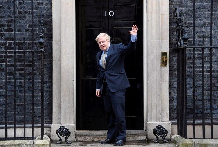 El primer ministro británico Boris Johnson saluda cuando llega a Downing Street 10 después de reunirse con la Reina en el Palacio de Buckingham para pedir permiso para formar gobierno (REUTERS/Toby Melville)
