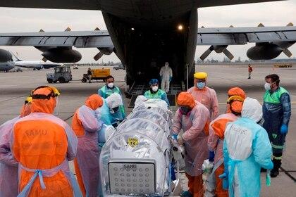 Personal sanitario de la Fuerza Aérea de Chile (FACH) e integrantes del Servicio de Atención Médica de Urgencia SAMU (de naranja) llevan a un avión a un paciente crítico de COVID-19 el 11 de junio de 2020 en Santiago (Chile) (EFE/Alberto Valdés)