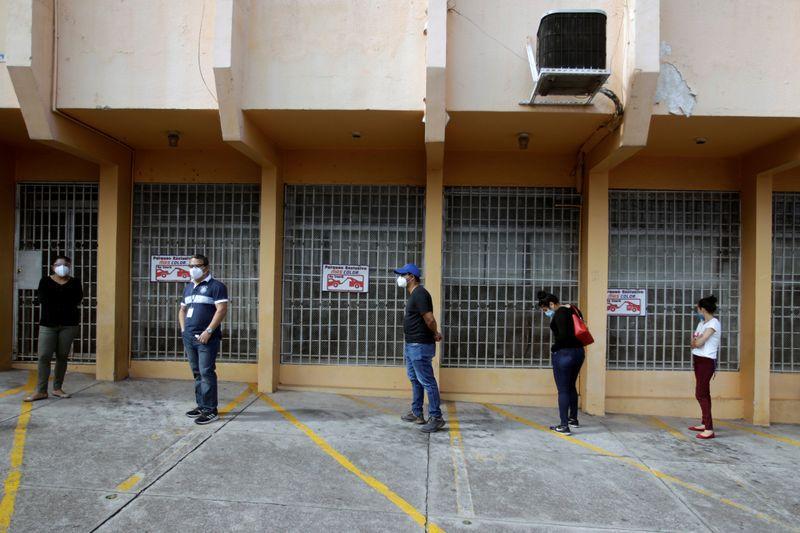 Personas mantienen distancia social mientras esperan para hacerse una prueba de detección del coronavirus afuera de un laboratorio en Tegucigalpa, Honduras (REUTERS/Jorge Cabrera)