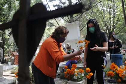 Integrantes de una familia decoran una tumba en el cementerio de Xilotepec, Xochimilco (Foto: Reuters/Henry Romero)