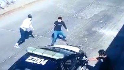 Segundos después, los tres se alejan y activan sus armas contra el policía (Fotografía: Captura de Pantalla/@TelevisaMorelos)