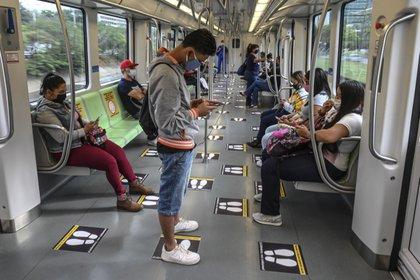 Personas usando tapabocas en el metro de Medellín. (Photo by Joaquin SARMIENTO / AFP)