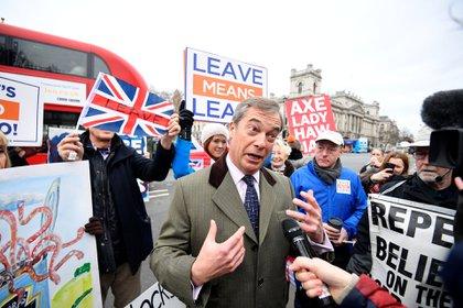 El ex líder del UKIP Nigel Farage habla a los medios de comunicación mientras los manifestantes a favor y en contra del proyecto de ley se manifiestan frente a la sede del Parlamento en Londres, Gran Bretaña, el 15 de enero de 2019. (Reuters)