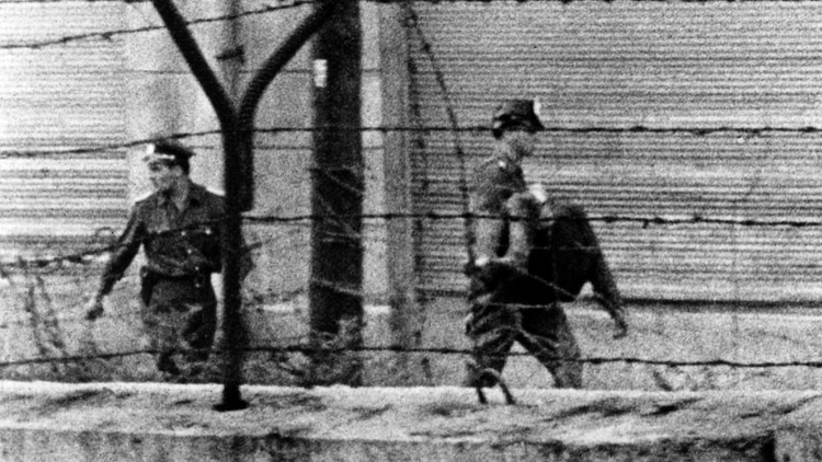 La policía se lleva el cuerpo de Peter, quien agonizó sin que nadie lo socorriera en el espacio conocido como Zona de la Muerte. Los oficiales habían disparado contra el joven de 18 años mientras él trataba de escapar de Berlín Oriental (Herbert Ernst/AP)