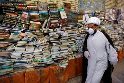 Un hombre musulmán chiíta lleva una máscara protectora, tras el brote de la enfermedad coronavirus (COVID-19), mientras camina junto a los libros religiosos durante el mes sagrado del Ramadán en Najaf, Irak, el 16 de mayo de 2020. REUTERS/Alaa Al-Marjani