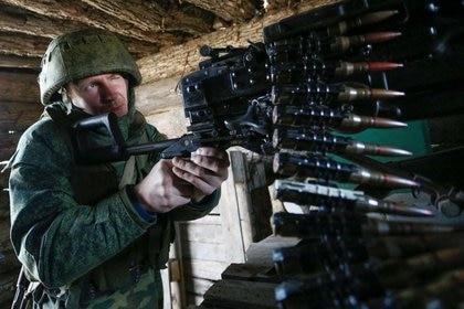 Un militante de la autoproclamada República Popular de Donetsk (DNR) apunta con un arma a las posiciones de combate en la línea de separación de las fuerzas armadas ucranianas al sur de la ciudad de Donetsk, controlada por los rebeldes, Ucrania