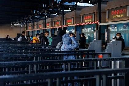 Pasajeros que portan mascarrillas ingresan a una estación de trenes de Pekín para asistir al Festival de la Primavera que marca el comienzo de las celebraciones por el Año Nuevo Lunar en Asia. Enero 28, 2021. REUTERS/Carlos Garcia Rawlins