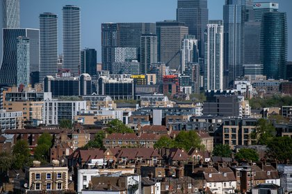 Residential properties stand in view of skyscrapers in the Canary Wharf business, financial and shopping district of London, U.K., on Tuesday, April 21, 2020. U.K. real estate agents called for help from the government as expectations for prices and market activity plunged. Photographer: Chris J. Ratcliffe/Bloomberg