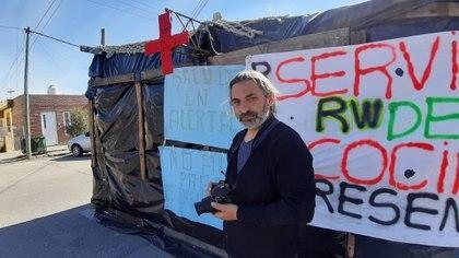 """Anibal Aguaisol sostiene su cámara frente al """"Centro de Atención Precaria"""" del Hospital Santa Teresita de Rawson en el que trabaja"""