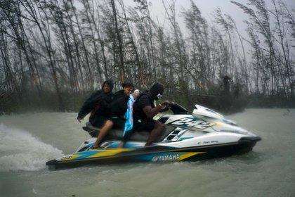 Tres pers0nas escapan en una moto acuática (AP)