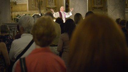 El sacerdote, oficiando la misa, ante los fieles de esta parroquia que pertenece a la religión católica apostólica romana