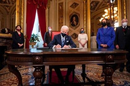 El presidente estadounidense Joe Biden firma sus primertos documentos oficiales (Jim Lo Scalzo/Pool via REUTERS)