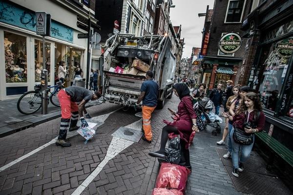 Los trabajadores recogen la basura en pleno centro de Ámsterdam. (Kadir van Lohuizen/Noor/The Washington Post)