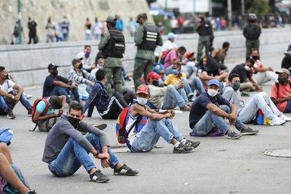 Personas son colocadas en medio de la calle por fuerzas de seguridad en el barrio de Petare como castigo por no respetar las medidas de distanciamiento social, en Caracas (REUTERS/Manaure Quintero)
