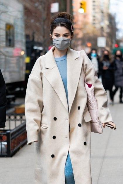 """Día de rodaje. Selena Gomez filmó una escena de  """"Only Murders in the Building"""". Para ello lució un vestido celeste y un tapado color cremita. Además, llevó su pelo recojido y tapabocas"""