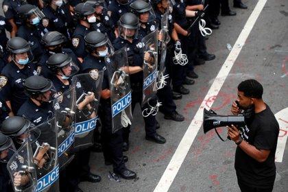 """Un manifestante se para frente a los oficiales del Departamento de Policía de Nueva York (NYPD) dentro de un área que se llama la """"Zona Autónoma del Ayuntamiento"""" que se ha establecido para protestar contra las fuerzas policiales y en apoyo de """"Black Lives Matter"""" (REUTERS / Andrew Kelly)"""