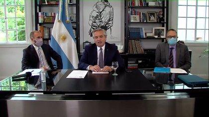 El presidente Alberto Fernández, flanqueado por los ministros Guzmány Kulfas, al dirigirse al Foro Económico Mundial