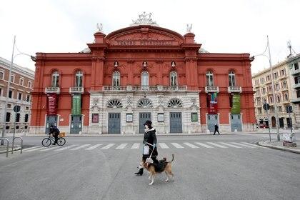 Una mujer pasea a su perro en Bari, Italia (Reuters)