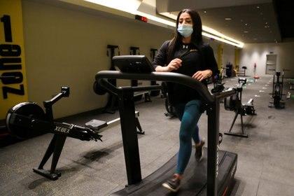 Una mujer hace ejercicios en un gimnasio utilizando un tapaboca