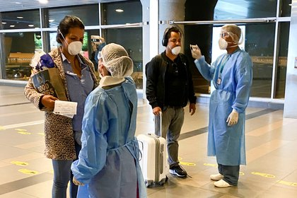 Medical staff of the Ministry of Health checks passenger's temperature, as a preventive measure in response to the spreading coronavirus disease (COVID-19), upon their arrival to El Dorado international airpot in Bogota, Colombia March 15, 2020. REUTERS/Luisa Gonzalez