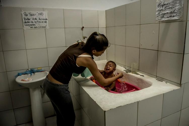 Alejandra Urquiola, de 17 años, baña a su hijo de 1 año, Yosneider Graterol, en los sanitarios del ala pediátrica del Hospital Central de San Cristóbal, en un intento por bajarle la fiebre. Credit. (Meridith Kohut/The New York Times)