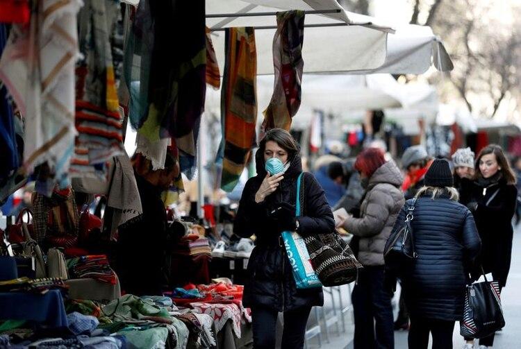 Una mujer con mascarilla protectora camina por un mercado callejero, en Milán, mientras un brote de coronavirus continúa creciendo en el norte de Italia. 27 de febrero de 2020. REUTERS/Yara Nardi.