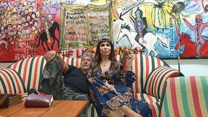 """Moria Casán y Humberto Poidomani, sentados delante del cuadro """"Apocalipsis Nice"""", que inspiró el vestido de """"la One"""""""