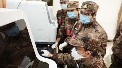 Científicos militares chinos observan un monitor en un laboratorio en el que se investiga los alcances del coronavirus COVID-19 (AMMS)