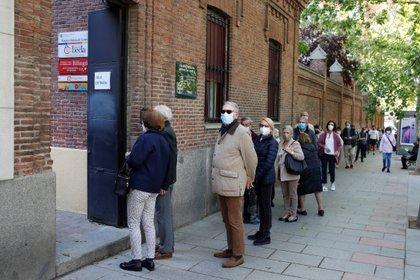 Varias personas esperan su turno para ejercer su derecho al voto en el colegio electoral de Nuestra Señora de Loreto en Madrid durante la jornada de comicios regionales (EFE)