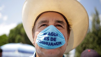 "FILE PHOTO: A man wearing a protective face mask attends a protest against the decision of the Mexican government to divert water from La Boquilla dam to the U.S., as part of a 1944 bilateral water treaty between the two countries, in Delicias, Chihuahua state, Mexico September 20, 2020. The writing reads, ""Water belongs to Chihuahua"". REUTERS/Jose Luis Gonzalez/File Photo"
