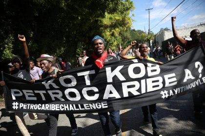 """Manifestantes sostienen una bandera con la leyenda """"¿Dónde está el dinero de Petrocaribe?""""(REUTERS/Andres Martinez Casares)"""