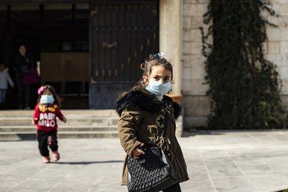 Dos niñas en Siria usan cubrebocas como medida preventiva. Niños misteriosamente se han salvado del coronavirus a nivel mundial (Delil Souleiman/AFP)