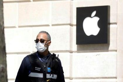 FOTO DE ARCHIVO: Un policía municipal con una mascarilla pasa junto a una tienda de Apple cerrada en la avenida Champs-Elysees en París en medio del confinamiento parra frenar el COVID-19 en Francia. 16 de abril de 2020 .REUTERS/Charles Platiau/File Photo