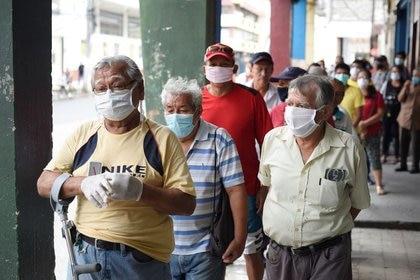 Personas mayores hacen fila para cobrar su pensión mensual antes del toque de queda impuesto por el Gobierno para frenar el avance de la enfermedad del coronavirus (COVID-19), en Guayaquil, Ecuador, 20 de marzo del 2020. REUTERS/Santiago Arcos