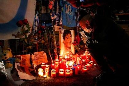 Un hombre enciende una vela en homenaje a la leyenda del fútbol mundial Diego Armando Maradona fuera del Stadio San Paolo en Nápoles, Italia (Reuters)