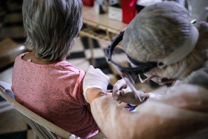 Una enfermera aplica a una mujer una vacuna contra la gripe.
