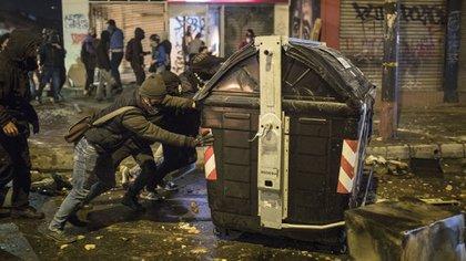Manifestantes arrastran un contenedor de basura (AP Photo/Ivan Valencia)