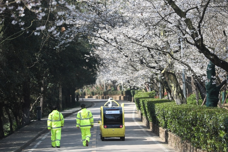 Personal de seguridad camina por las calles de Wuhan (China Daily via REUTERS)