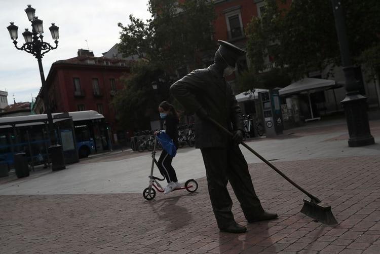 Una niña en patineta pasa junto a una estatua decorada con una mascarilla tras el levantamiento parcial de las medidas de confinamiento impuestas durante el brote de la enfermedad del nuevo coronavirus (COVID-19) en Madrid, España, el 27 de abril (REUTERS/Susana Vera)