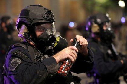 Un agente federal con balas de gas pimienta durante las protestas en Portland (REUTERS/Caitlin Ochs)