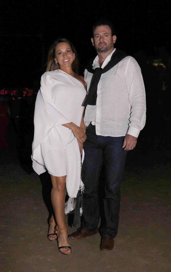 José Urtubey, con sweater negro en los hombros sobre una camisa de lino negra, y su mujer Soledad, quien lo acompañó con un vestido de un solo hombro en blanco.