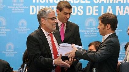 Axel Kicillof le entrega las bases del Presupuesto 2016 al diputado Roberto Feletti. Telam 162